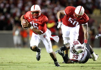 RALEIGH, NC - SEPTEMBER 3:  Quarterback Russell Wilson #16 of the North Carolina State Wolfpack scrambles for yards after avoiding the tackle by Nathan Pepper #95 of the South Carolina Gamecocks during the game at Carter-Finley Stadium on September 3, 200