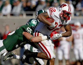 EAST LANSING, MI - NOVEMBER 01:  John Clay #32 of the Wisconsin Badgers tries for extra yards during a third quarter run in front of Adam Decker #55 of the Michigan State Spartans on November 1, 2008 at Spartan Stadium in East Lansing, Michigan. Michigan