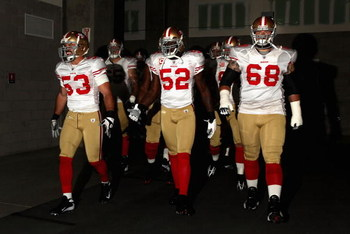 GLENDALE, AZ - SEPTEMBER 13:  (L-R) Jeff Ulbrich #53, Patrick Willis #52 and Adam Snyder #68 of the San Francisco 49ers walk out onto the field prior to the NFL game against the Arizona Cardinals at the Universtity of Phoenix Stadium on September 13, 2009