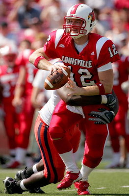 LOUISVILLE, KY - SEPTEMBER 22: Quarterback Brian Brohm #12 of the Louisville Cardinals looks for an outlet pass while being tackled by Arthur Jones #97 of the Syracuse Orange at Papa John's Cardinal Stadium September 22, 2007 in Louisville, Kentucky.  (Ph