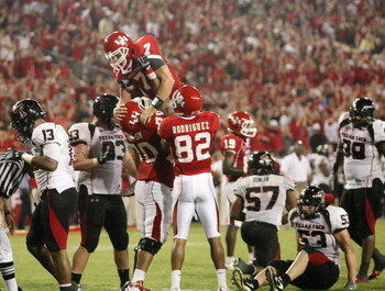 HOUSTON - SEPTEMBER 26:  Quarterback Case Keenum #7 of the Houston Cougars is lifted in the air after Kennum scored a 4 yard touchdown run to give the Cougars a 29 to 28 win over the Texas Tech Red Raiders at Robertson Stadium on September 26, 2009 in Hou