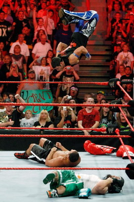 LAS VEGAS - AUGUST 24:  Wrestler Evan Bourne jumps off the ropes at wrestler Chavo Guerrero (C) as wrestler Hornswoggle lies in the foreground during the WWE Monday Night Raw show at the Thomas & Mack Center August 24, 2009 in Las Vegas, Nevada.  (Photo b