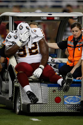 DETROIT, MI - SEPTEMBER 27: Defensive tackle Albert Haynesworth #92 of the Washington Redskins sits on a cart as he is taken off the field after an injury in the first half against the Detroit Lions at Ford Field on September 27, 2009 in Detroit, Michigan