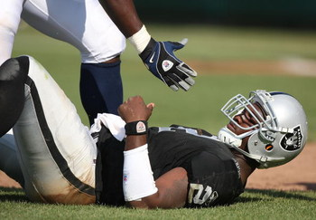 OAKLAND, CA - SEPTEMBER 27:  JaMarcus Russell #2 of the Oakland Raiders is helped up after getting hit against the Denver Broncos on September 27, 2009 during an NFL game at the Oakland-Alameda County Coliseum in Oakland, California.  (Photo by Jed Jacobs