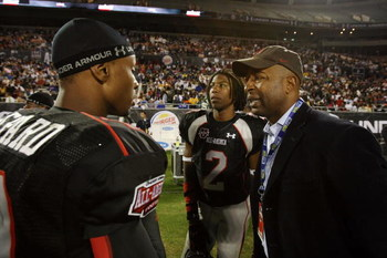 ORLANDO, FL - JANUARY 04:  Former NFL player Chris Carter, R,  and quarterback Russell Shepard #10 of the black team talk on the sideline as Carter's son Duron Carter #2 looks on during the All America Under Armour Football Game at Florida Citrus Bowl on