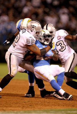 OAKLAND, CA - SEPTEMBER 14:  LaDainian Tomlinson #21 of the San Diego Chargers is tackled by Richard Seymour #92 of the Oakland Raiders during their game on September 14, 2009 at the Oakland-Alameda County Coliseum in Oakland, California.  (Photo by Ezra