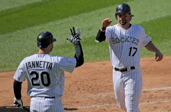 DENVER - OCTOBER 01:  Todd Helton #17 of the Colorado Rockies is welcomed home by Chris Iannetta #20 after he scored on an RBI double by Garrett Atkins off of starting pitcher Manny Parra #26 of the Milwaukee Brewers to give the Rockies a 3-0 lead in the