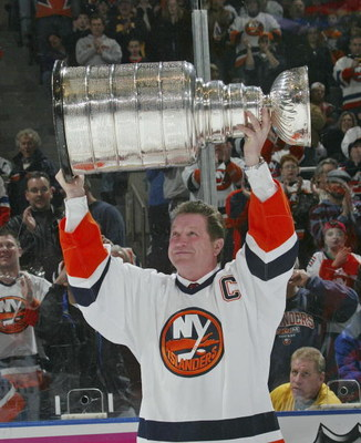 UNIONDALE, NY - MARCH 4:  Denis Potvin #5, formerly of the New York Islanders, holds up the Stanley Cup during a ceremony honoring the 25th anniversary of the Islanders first Stanley Cup victory held on March 4, 2006 at the Nassau Coliseum in Uniondale, N