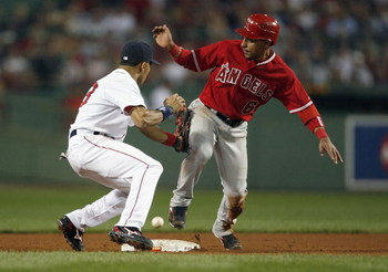 BOSTON - OCTOBER 5:  Julio Lugo #23 of the Boston Red Sox looks for the ball as Maicer Izturis #6 of the Los Angeles Angels steals second during Game 2 of the American League Division Series at Fenway Park October 5, 2007 in Boston, Massachusetts.   (Phot