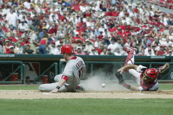 ST. LOUIS - JUNE 20:  Darin Erstad #17 of the Anaheim Angels slides safely into home plate as Mike Matheny #22 of the St. Louis Cardinals drops the ball at Busch Stadium in St. Louis, Missouri on June 20, 2002.  (Photo by Elsa/Getty Images)