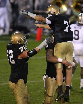 SOUTH BEND, IN - OCTOBER 03: Jimmy Clausen #7 of the Notre Dame Fighting Irish is lifted in the air by teammate Eric Olsen #55 as Paul Duncan #72 joins the celebration after a 4th quarter touchdown against the Washington Huskies on October 3, 2009 at Notr