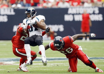 HOUSTON - SEPTEMBER 27: Wide receiver Torry Holt #81 of the Jacksonville Jaguars is tripped up by free safety Eugene Wilson #26 and cornerback Dunta Robinson #23 of the Houston Texans at Reliant Stadium on September 27, 2009 in Houston, Texas.  (Photo by