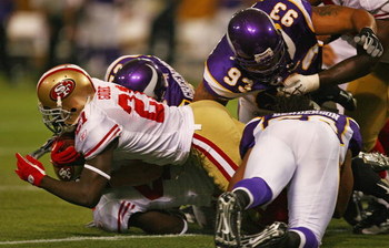 MINNEAPOLIS - SEPTEMBER 27: Frank Gore #21 of the San Francisco 49ers is tackled by Chad Greenway #52, Kevin Williams #93 and E.J. Henderson #56 of the Minnesota Vikings at the Hubert H. Humphrey Metrodome on September 27, 2009 in Minneapolis, Minnesota.