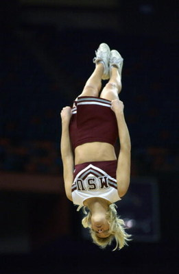 NEW ORLEANS - MARCH 15:  A Mississippi State cheerleader is flipped into the air during semifinal action in the SEC Men's Basketball Tournament against Louisiana State Univerity at the Louisiana Superdome on March 15, 2003 in New Orleans, Louisiana. Missi