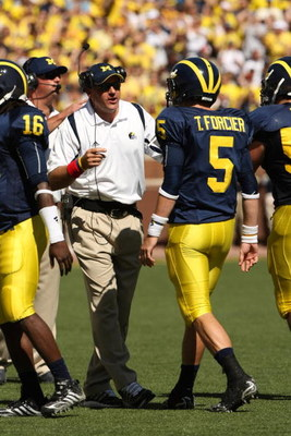 ANN ARBOR, MI - SEPTEMBER 19:  Head coach Rich Rodriguez of the Michigan Wolverines talks with quarterback Tate Forcier #5 during the game with the Eastern Michigan Eagles at Michigan Stadium on September 19, 2009 in Ann Arbor, Michigan.  Michigan won 45-