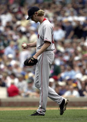 CHICAGO - JUNE 10:  Starting pitcher Bronson Arroyo #61 of the Boston Red Sox reacts after giving up runs in the third inning to the Chicago Cubs on June 10, 2005 at Wrigley Field in Chicago, Illinois. The Cubs defeated the Red Sox 14-6.  (Photo by Jonath