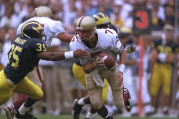 21 Sep 1996:  Quarterback Matt Hasselbeck #7 of the Boston College Eagles looks up field for an open receiver as he rolls out of the pocket to avoid the pursuing defensive back Chuck Winter #35 of the Michigan Wolverines during a play in the Eagles 20-14
