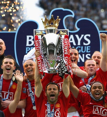 WIGAN, UNITED KINGDOM - MAY 11:  Ryan Giggs of Manchester United  lifts the Barclays Premier League trophy as his team mates celebrate following their victory at the end of the Barclays Premier League match between Wigan Athletic and Manchester United at