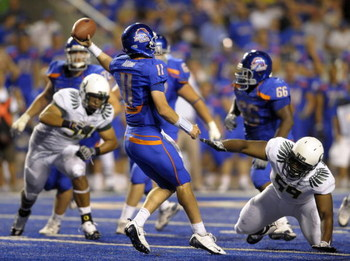 BOISE, ID - SEPTEMBER 3: Quarterback Kellen Moore #11 of the Boise State Broncos gets off a pass under the rush of Zac Clark #99 and Terrance Montgomery #59 of the Oregon Ducks in the fourth quarter of the game on September 3, 2009 at Bronco Stadium in Bo