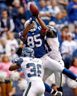 INDIANAPOLIS - OCTOBER 04:  Pierre Garcon #85 of the Indianapolis Colts reaches up for the ball while defended by Kelly Jennings #21 of the Seattle Seahawks at Lucas Oil Stadium on October 4, 2009 in Indianapolis, Indiana. The Colts won 34-17.  (Photo by