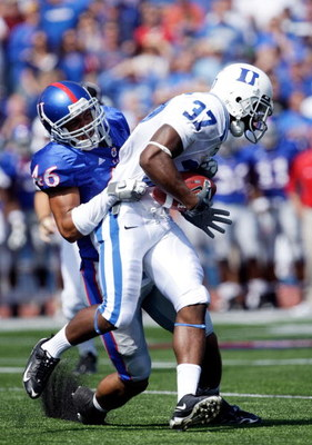 LAWRENCE, KS - SEPTEMBER 19:  Johnny Williams #37 of the Duke Blue Devils carries the ball as Justin Thornton #46 of the Kansas Jayhawks defends during the 1st half of the game at Kivisto Field at Memorial Stadium on September 19, 2009 in Lawrence, Kansas