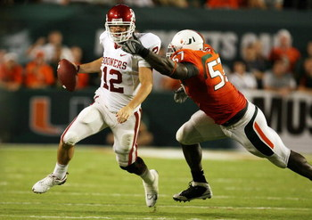 FORT LAUDERDALE, FL - OCTOBER 03: Quarterback Landry Jones #12 of the Oklahoma Sooners is sacked by defensive lineman Allen Bailey #57 of the Miami Hurricanes knocked down a pass attempt at Land Shark Stadium on October 3, 2009 in Fort Lauderdale, Florida