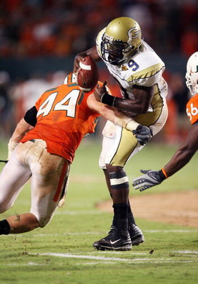 FORT LAUDERDALE, FL - SEPTEMBER 17:  Quarterback Josh Nesbitt #9 of the Georgia Tech Yellow Jackets is brought down by linebacker Colin McCarthy #44 of the Miami Hurricanes at Land Shark Stadium on September 17, 2009 in Fort Lauderdale, Florida. Miami def
