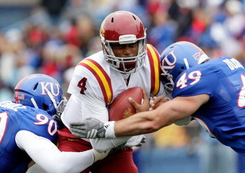 LAWRENCE, KS - OCTOBER 10:  Quarterback Austen Arnaud #4 of the Iowa State Cyclones is hit by Maxwell Onyegbule #90 and Drew Dudley #49 of the Kansas Jayhawks while scrambling during the game on October 10, 2009 at Memorial Stadium in Lawrence, Kansas.  (