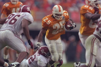 26 Oct 1996: Running back Jay Graham #25 of the Tennessee Volunteers tries to run through the tackle of defensive lineman Tyrell Buckner #92 of the Alabama Crimson Tide as defense lineman Michael Myers #96 closes during the Volunteers 20-13 victory over t