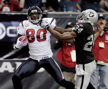 HOUSTON - OCTOBER 04:  Wide receiver Andre Johnson #80 of the Houston Texans gives safety Michael Huff #24 of the Oakland Raiders a stiff arm after making a 62 yard reception at Reliant Stadium on October 4, 2009 in Houston, Texas.  (Photo by Bob Levey/Ge
