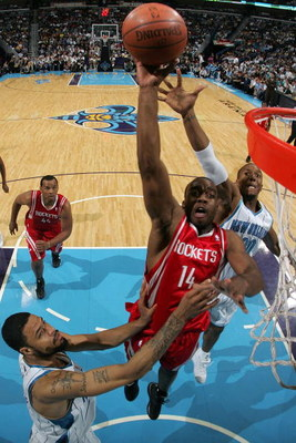 NEW ORLEANS - DECEMBER 26:  Carl Landry #14 of the Houston Rockets makes a shot over David West #30 and Tyson Chandler #6 of the New Orleans Hornets on December 26, 2008 at the New Orleans Arena in New Orleans, Louisiana.   The Hornets defeated the Rocket