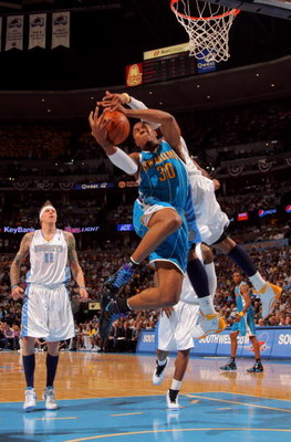 DENVER - APRIL 29:  David West #30 of the New Orleans Hornets is fouled by Carmelo Anthony #15 of the Denver Nuggets in Game Five of the Western Conference Quarterfinals during the 2009 NBA Playoffs at Pepsi Center on April 29, 2009 in Denver, Colorado. T