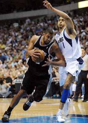 DALLAS - APRIL 25:  Forward Tim Duncan #21 of the San Antonio Spurs dribbles the ball past Ryan Hollins #1 of the Dallas Mavericks in Game Four of the Western Conference Quarterfinals during the 2009 NBA Playoffs at American Airlines Center on April 25, 2
