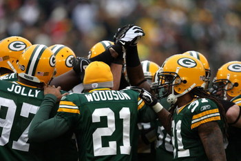 GREEN BAY, WI - NOVEMBER 30:  (L-R) Johnny Jolly #97, Charles Woodson #21 and Al Harris #31 of the Green Bay Packers huddle up with their defensive teammates against the Carolina Panthers at Lambeau Field on November 30, 2008 in Green Bay, Wisconsin. The