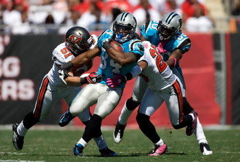 TAMPA, FL - OCTOBER 18:  Running back DeAngelo Williams #34 of the Carolina Panthers is tackled by defenders Barrett Ruud #51 and Ronde Barber #20 of the Tampa Bay Buccaneers during the game at Raymond James Stadium on October 18, 2009 in Tampa, Florida.