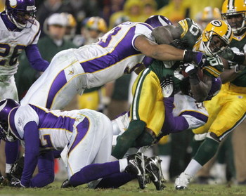 GREEN BAY, WI - DECEMBER 21:  Donald Driver #80 of the Green Bay Packers fights for yardage as he is tackled by Kevin Williams #93 and Dwight Smith #24 of the Minnesota Vikings on December 21, 2006 at Lambeau Field in Green Bay, Wisconsin. (Photo by Jonat
