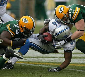 GREEN BAY, WI - OCTOBER 18: Kevin Smith #34 of the Detroit Lions is tackled by Ryan Pickett #79 and A.J. Hawk #50 of the Green Bay Packers at Lambeau Field on October 18, 2009 in Green Bay, Wisconsin. The Packers defeated the Lions 26-0. (Photo by Jonatha