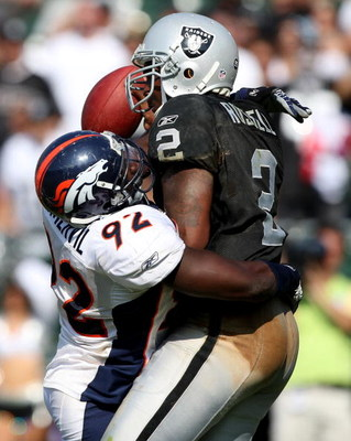 OAKLAND, CA - SEPTEMBER 27:  JaMarcus Russell #2 of the Oakland Raiders is sacked by Elvis Dumervil #92 of the Denver Broncos on September 27, 2009 during an NFL game at the Oakland-Alameda County Coliseum in Oakland, California.  (Photo by Jed Jacobsohn/