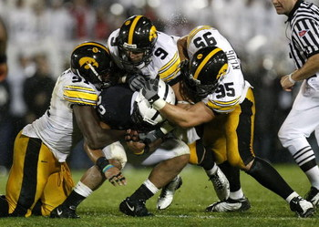 STATE COLLEGE, PA - SEPTEMBER 26:  Evan Royster #22 of the Penn State Nittnay Lions is tackled by Karl Klug #95, Tyler Sash #9, and Broderick Binns #91 of the Iowa Hawkeye's on September 26, 2009 at Beaver Stadium in State College, Pennsylvania. Iowa won