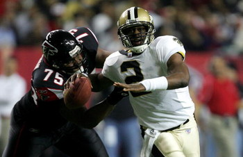ATLANTA - DECEMBER 12:  Aaron Brooks #2 of the New Orleans Saints is chased from behind by Rod Coleman #75 of the Atlanta Falcons in NFL action December 12, 2005 at the Georgia Dome in Atlanta, Georgia.  (Photo By Streeter Lecka)