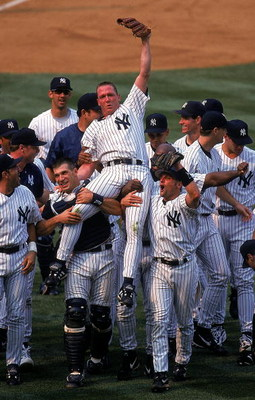 18 Jul 1999: David Cone #36 of the New York Yankees celebrates as his teammates lift him after winning the game against the Montreal Expos at Yankee Stadium in Bronx, New York. The Yankees defeated the Expos 6-0.