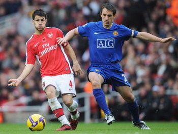 LONDON - NOVEMBER 08:   Francesc Fabregas of Arsenal holds off Gary Neville of Manchester United as he passes to Samir Nasri to score their second goal during the Barclays Premier League match between Arsenal and Manchester United at the Emirates Stadium