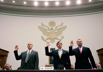 WASHINGTON - FEBRUARY 13:  Major League Baseball pitcher Roger Clemens (R), Charlie Scheeler, investigator on former Sen. George Mitchell's staff (C) and and former Major League Baseball strength and conditioning coach Brian McNamee (L) raise their right