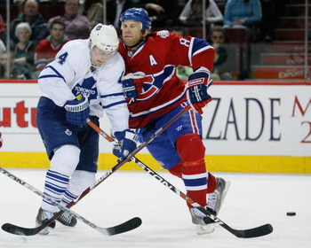 MONTREAL- JANUARY 8:  Mike Komisarek #8 of the Montreal Canadiens body checks Matt Stajan #14 of the Toronto Maple Leafs at the Bell Centre on January 08, 2009 in Montreal, Quebec, Canada.   The Montreal Canadiens defeated the Toronto Maple Leafs 6-2.  (P