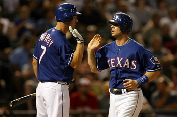 ARLINGTON, TX - JULY 11:  Michael Young #10 of the Texas Rangers celebrates scoring a run with David Murphy #7 during action against the Chicago White Sox in the 6th inning on July 11, 2008 at Rangers Ballpark in Arlington, Texas.  (Photo by Ronald Martin