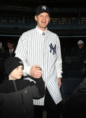 NEW YORK - DECEMBER 18: A.J. Burnett walks onto the field with his son after a press conference to announce his signing to the New York Yankees at Yankee Stadium on December 18, 2008  in the Bronx borough of New York City.  (Photo by Nick Laham/Getty Imag