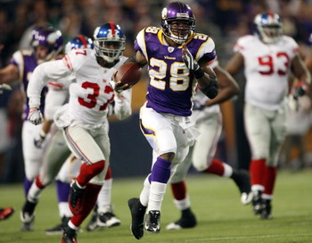 MINNEAPOLIS - DECEMBER 28:   Adrian Peterson #28 of the Minnesota Vikings runs the ball in for a touchdown as James Butler of the New York Giants defends on December 28, 2008 at the Hubert H. Humphrey Metrodome in Minneapolis, Minnesota. The Vikings defea