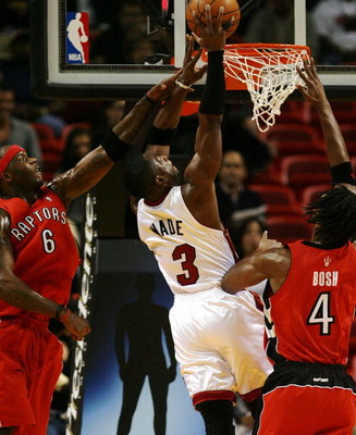 MIAMI - NOVEMBER 19:  Dwyane Wade #3 of the Miami Heat dunks over Chris Bosh #4 and Jermaine O'Neal #6 of the Toronto Raptors at American Airlines Arena on November 19, 2008 in Miami, Florida. The Raptors defeated the Heat 101-95. NOTE TO USER: User expre