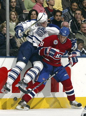 TORONTO - NOVEMBER 11:   Alexei Ponikarovsky #23 of the Toronto Maple Leafs checks Mike Komisarek #8 of the Montreal Canadiens during their NHL game at the Air Canada Centre on November 11, 2006 in Toronto, Ontario. The Leafs beat the Canadiens 5-1.  (Pho