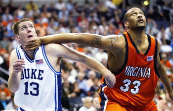 WASHINGTON - MARCH 11:  Lee Melchionni #13 of the Duke Blue Devils gets a hand to the chin from Devin Smith #33 of the Virginia Cavaliers during their second round ACC Tournament game at the MCI Center on March 11, 2005 in Washington, DC.  (Photo by Doug